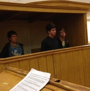 Joshua Slade stands in the box, watched by the constable and William Heddings, accused of stealing a pig from the late Reverend Waterhouse